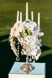 Wedding decoration with flowers and candle on sunny day in cere Royalty Free Stock Photography