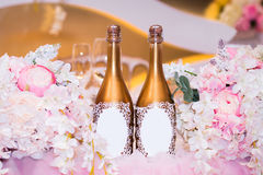 Wedding decoration of flowers and champagne. The wedding table is decorated with bouquets of peonies and champagne Royalty Free Stock Photos