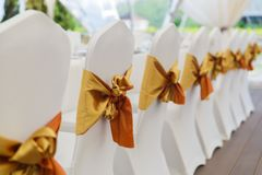 Wedding decoration, and golden ribbons decorate the chairs for guests stock images