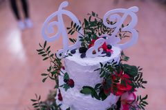Wedding decoration letter D & B on the Beautiful white wedding Cake with Pink flowers and greenery. Wedding Royalty Free Stock Image