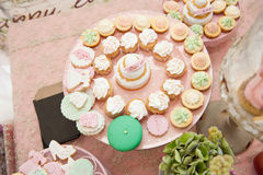 Wedding decoration with pastel colored cupcakes, meringues, muffins and macarons Royalty Free Stock Photo