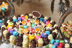 Wedding decoration with pastel colored cupcakes, meringues, muffins and macarons Stock Photography