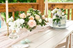 Wedding decoration table in the garden, floral arrangement,candles In the style vintage on outdoor. Wedding cake with flowers.