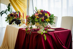 Wedding decoration table in the hall. Beautiful design wedding table, plates with gold foil and garnets Stock Image