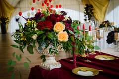 Wedding decoration table in the hall. Beautiful design wedding table, plates with gold foil and garnets Royalty Free Stock Image