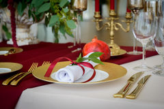 Wedding decoration table in the hall. Beautiful design wedding table, plates with gold foil and garnets Stock Photo