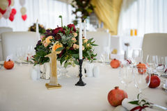 Wedding decoration table in the hall. Beautiful design wedding table, plates with gold foil and garnets Stock Photos