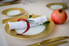 Wedding decoration table in the hall. Beautiful design wedding table, plates with gold foil and garnets Royalty Free Stock Images