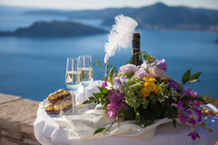 Wedding decorations above sea, mountains. Wineglasses, bottle of. Champagne, candies, bouquet from pink, white, flowers are on table for wedding ceremony royalty free stock photos