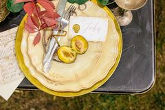 Wedding decorations in the autumn. With plates, leaves and plum stock image