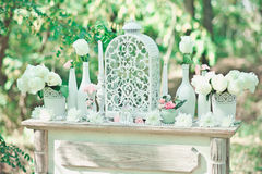 Wedding decorations for the ceremony in white flowers on green background, candles, tableware Royalty Free Stock Image