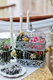 Wedding decorations. Flowers and candles in a cage on the table stock images