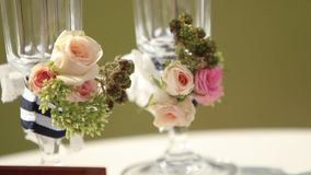 Wedding decorations for outdoor wedding ceremony. Glasses decorated with rorses and berries. stock video footage