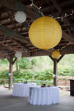 Wedding decorations. Wedding reception decorations in a pavilion setting, with lights hanging from ceiling and table cloths Royalty Free Stock Images