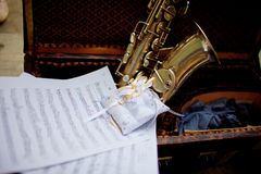 Wedding decorations. Wedding rings on a pillow lies in a suitcase together with notes and saxophone stock photos