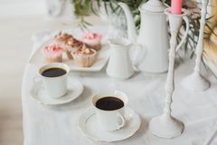 Wedding decorations zone - white table with bouquet and cupcakes Royalty Free Stock Images