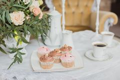 Wedding decorations zone - white table with bouquet and cupcakes Stock Image