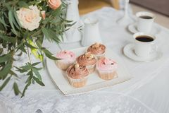 Wedding decorations zone - white table with bouquet and cupcakes Stock Photos
