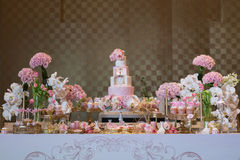 Wedding dessert area. Tiered wedding cake and cupcakes at outdoor wedding party Stock Images