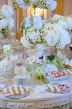 Wedding dessert table with cakes and white flowers. Glasses and plates stock photo