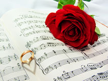 Wedding detail. Sheet music of the Wedding March with roses and rings royalty free stock photos
