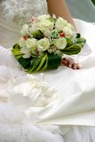 Wedding detail - bouqet. A bride holding her bouquet on the dress Stock Photo