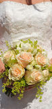 Wedding, Detail of a Bride with Apricot Roses. Details of a Wedding Bride White Wedding dress Apricot Roses and yellow small flowers in her bouquet Stock Photography
