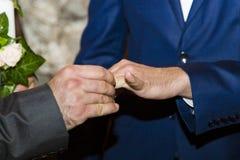 Wedding detail. Godfather putting the ring on bridegroom finger Royalty Free Stock Image