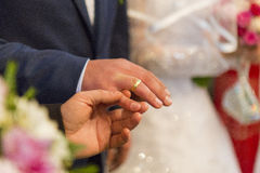 Wedding detail. Priest putting the ring on bridegroom finger royalty free stock photography