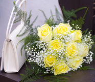 Wedding details. Wedding flower and hanbag is laying on a table Royalty Free Stock Images