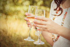 Wedding details. The bride is holding glasses of champagne Royalty Free Stock Images