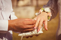 Wedding details. The bridegroom puts the ring on the bride Stock Image