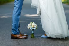 Wedding details: classic brown and blue shoes of bride and groom. Bouquet of roses standing on the ground between them. Newlyweds. Standing in front of each Stock Photography