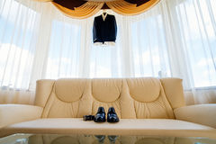 Wedding details. Groom accessories. Shoes and belt on leather sofa under a suit hanging on window Royalty Free Stock Photo