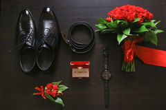 Wedding details. Groom accessories. Shoes, rings, belt, boutonniere and watch on table. Stock Images