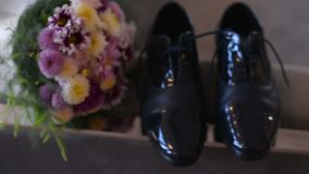 Grooms wedding shoes and bouquet of flowers