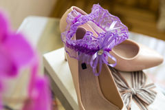 Wedding details. Purple Garter on Bride`s Slippers. Box with a gift Royalty Free Stock Image
