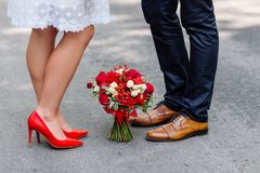 Wedding details: stylish red and brown shoes of bride and groom. Bouquet of roses standing on the ground between them. Newlyweds s. Tanding in front of each Stock Image