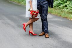 Wedding details: stylish red and brown shoes of bride and groom. Newlyweds standing in front of each other. Bridal bouquet of rose. S in the hands Stock Photos