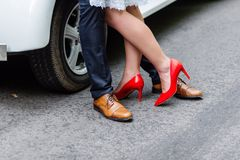 Wedding details: stylish red and brown shoes of bride and groom. Newlyweds standing in front of each other near the car.  Royalty Free Stock Photo