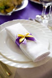 Wedding doily white with purple, yellow bowknot, decoration on the plate on the table Stock Image