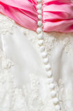 Wedding  drees. Fragment of embroidered wedding dress with pink scarf Stock Photos