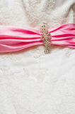 Wedding  drees. Fragment of embroidered wedding dress with pink scarf Stock Photography
