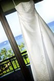 Wedding Dress. Hanging in window, with Waikiki Oahu Hawaii as the back ground Royalty Free Stock Photo