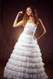 Wedding dress. Fashion model wearing wedding dress at brown studio background Stock Image