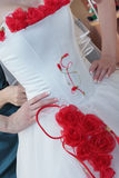 Wedding Dress. With a decoration of red roses on the bride Royalty Free Stock Photography