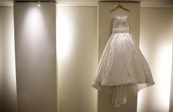 Wedding Dress. White satin Wedding Dress Hanging on Wall Stock Photos