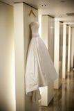 Wedding Dress. White satin Wedding Dress Hanging on Wall Stock Photo