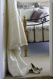 Wedding dress. And shoes in bedroom Royalty Free Stock Image