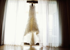Wedding dress. A classic white wedding dress hanging in the window Royalty Free Stock Photography